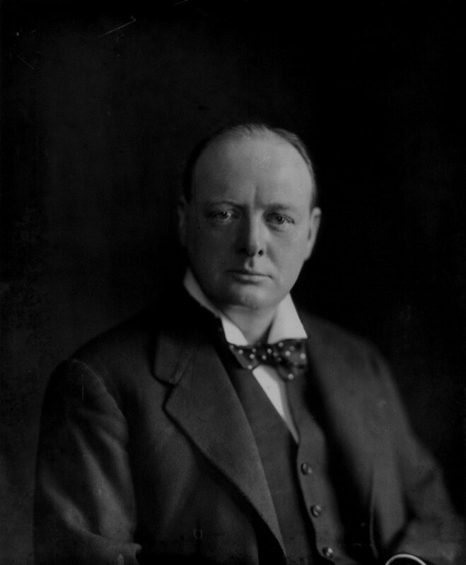 Portrait of head and shoulders of balding man wearing a suit and bowtie