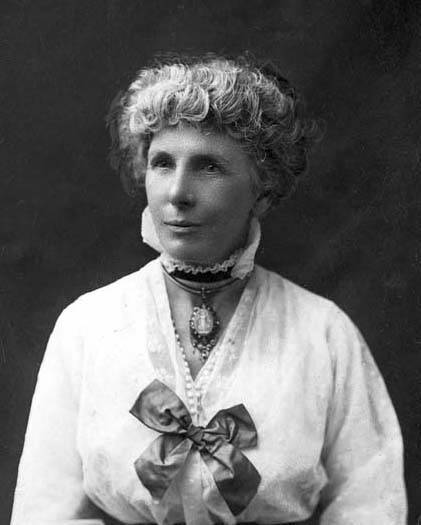 Head and upper body of woman, formally dressed with hair up, wearing collar choker, and necklace with large oval pendant, large bow on front of white blouse, black and white photograph
