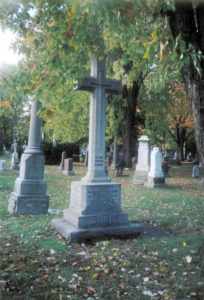 Grey cross on pedestal, other headstones in the background, many trees with autumnal coloured leaves