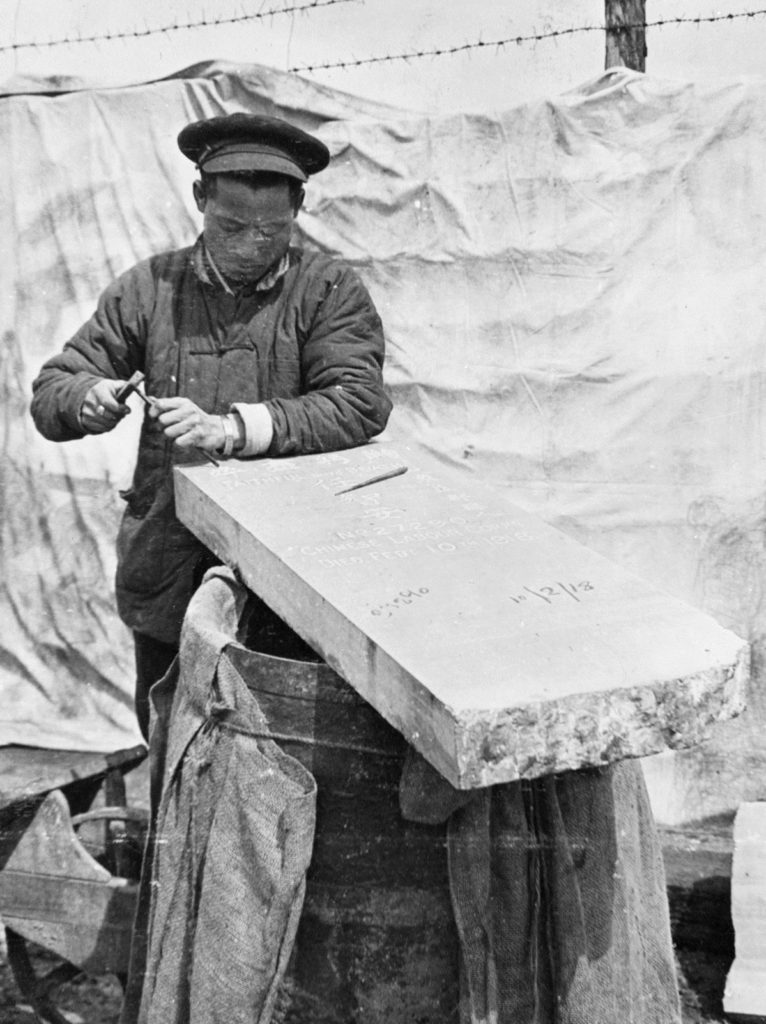 Man in peaked hat chiselling a slab of white stone, part of another headstone to his right, barbed wire fence partly covered by cloth behind him, black and white photograph