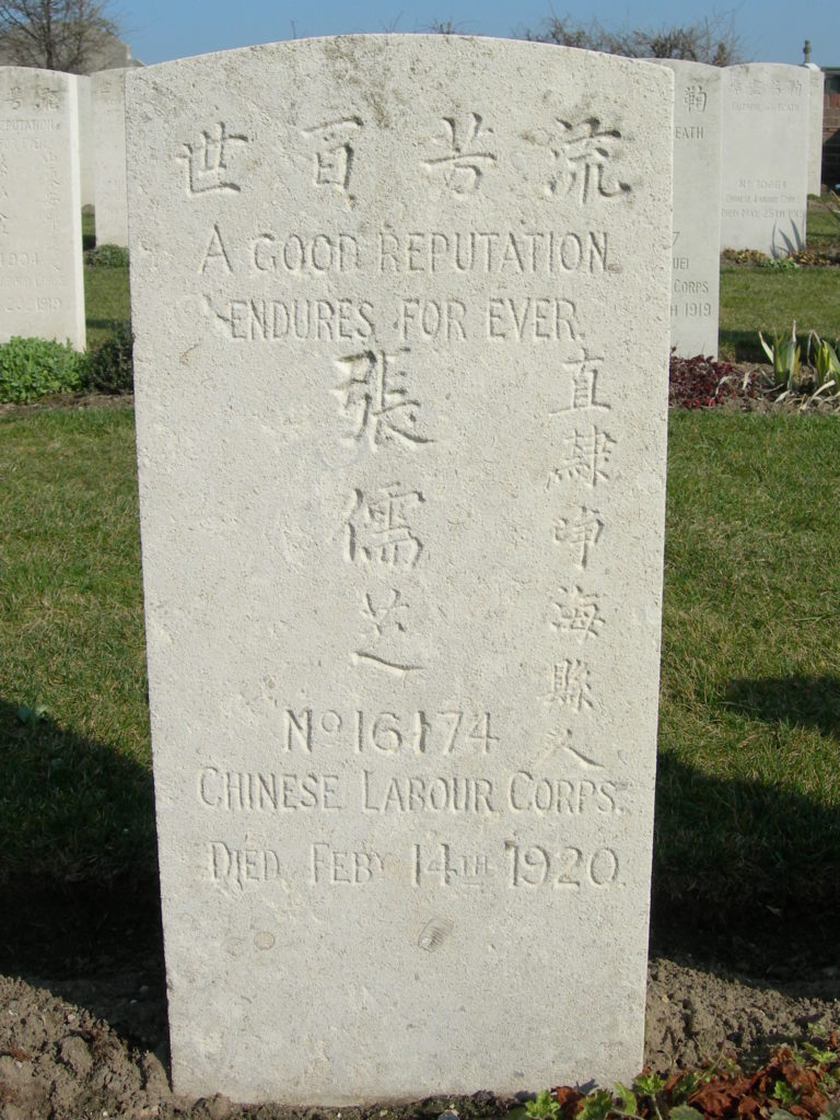 Close-up of white headstone in a cemetery, other headstones in the background