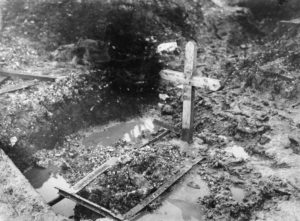 Wooden cross on make-shift grave in waterlogged mud, black and white photograph