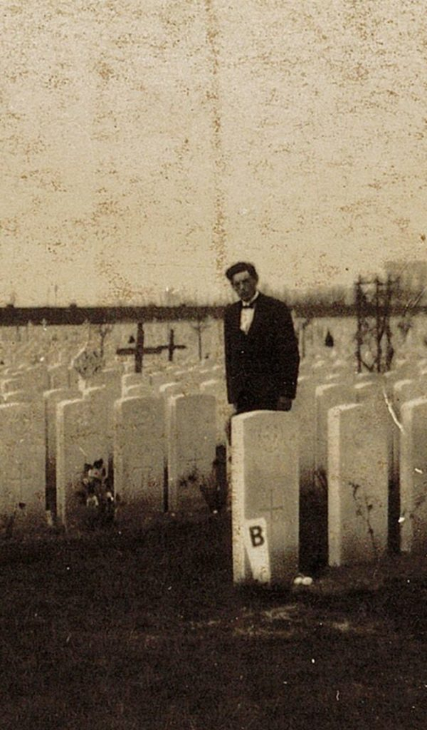 Man standing amongst rows of headstones, small leafless tree in the left foreground, black and white photograph