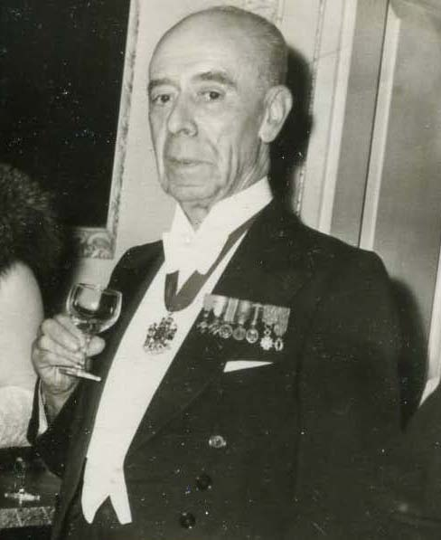 Bald man in evening dress with military medals, holding a wine glass, to his right is the shoulder and hair of a woman, black and white photograph