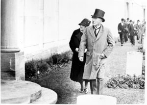 Man and woman in overcoats and hats looking at white pillar, headstones in front and behind them, and a long white wall, in the background a group of men in hats are walking towards them, black and white photograph