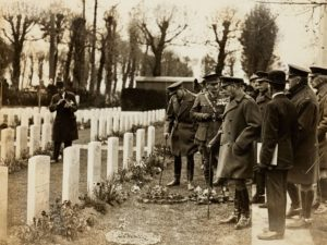 Group of men, some in uniform, looking at rows of headstones
