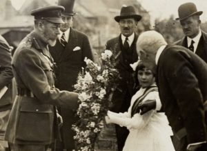 Girl in white dress handing large wreath of flowers to man in military uniform, other men in civilian clothing looking on