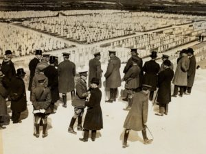 Group of men, some in uniform, looking at many rows of headstones