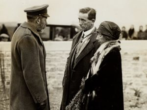 Man and woman talking to man in military uniform
