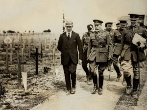 Group of men, some in uniform, walking past rows of wooden crosses